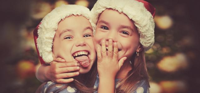 zwei lachende Kinder mit Weihnachtsmützen