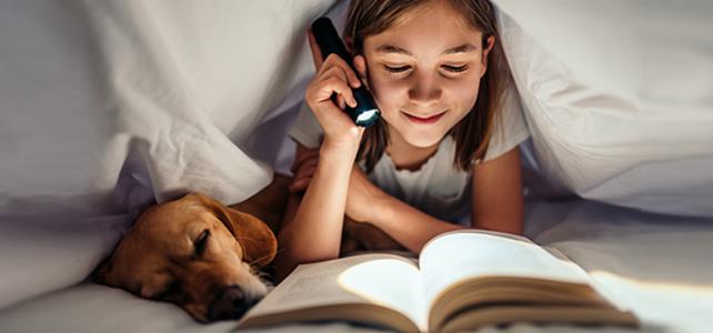 Mädchen liest mit Taschenlampe
